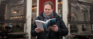 Portret van Mark Hoogstad met zijn laatste boek in de hand. Foto: Marwan Magroun
